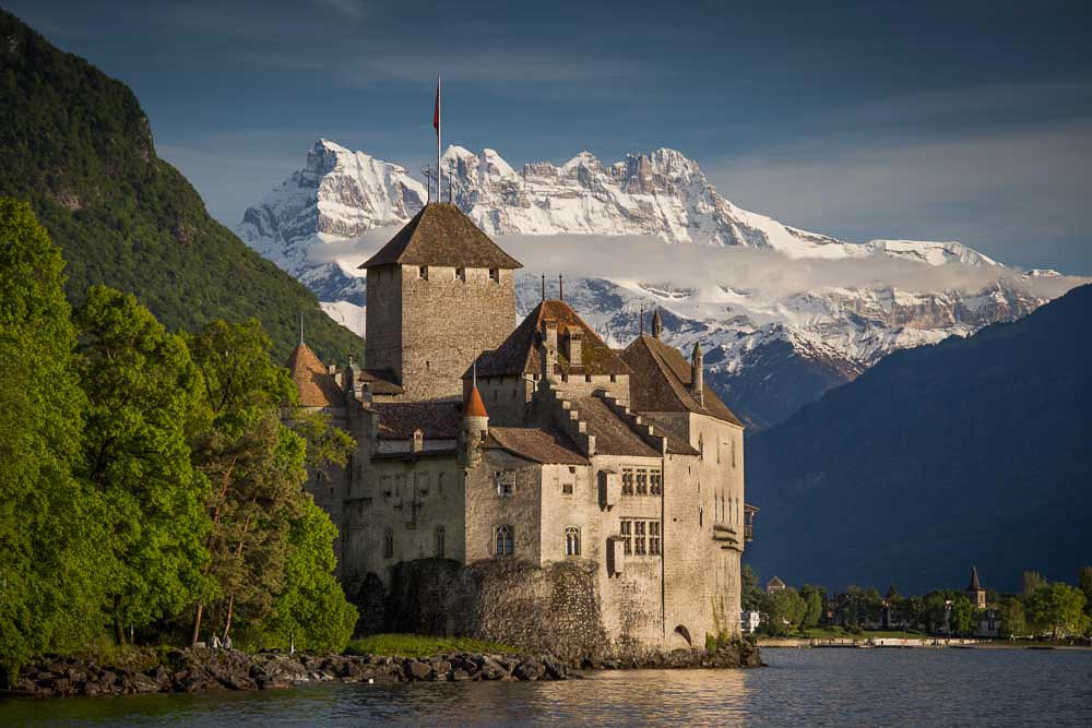 Chillon Castle on Lake Geneva with Alps route backdrop. Photo copyright Derry Brabbs. Used with permission.